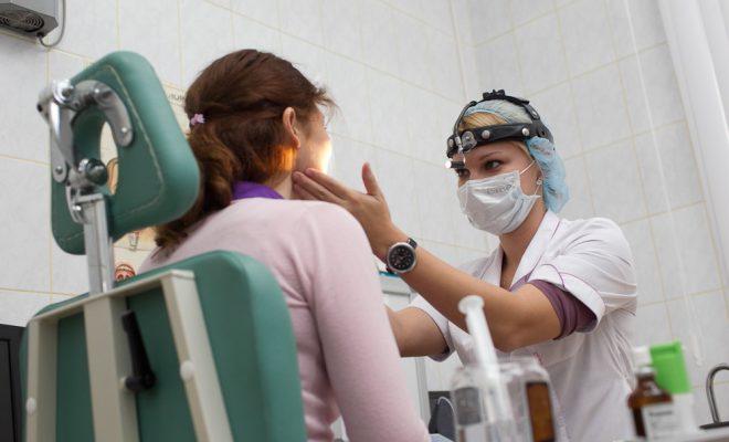 Врач диагностирует заболевание с помощью фарингоскопии.